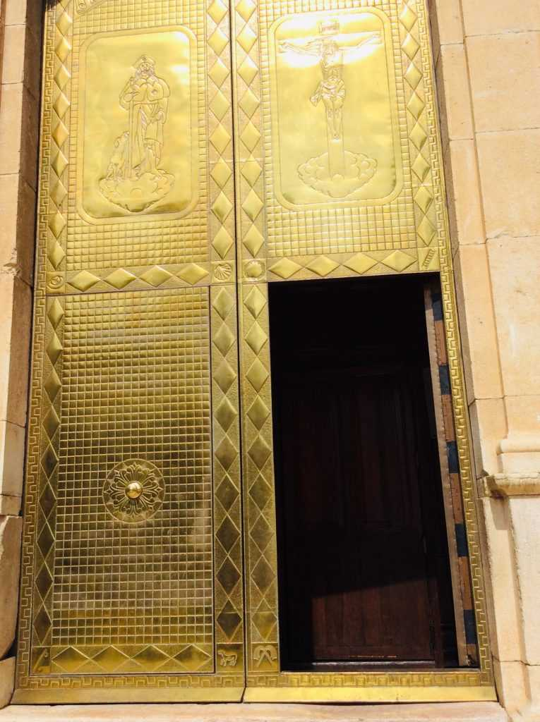 Golden entry door of San Roc Parish Church in Oliva, Valencia, Spain